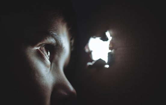 Closeup photo of a child looking through a hole cardboard