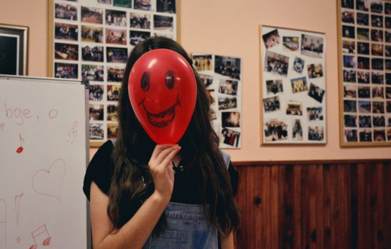 Happy face balloon hiding face