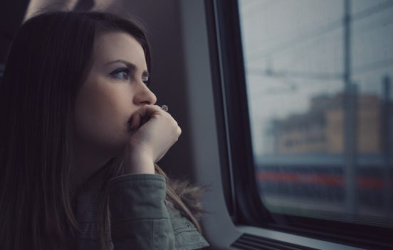 Closeup photo of a young woman looking ambivalently out of a train window on a grey day