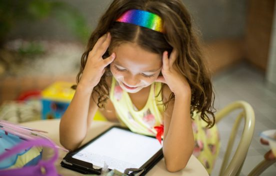 child looking at electronic tablet