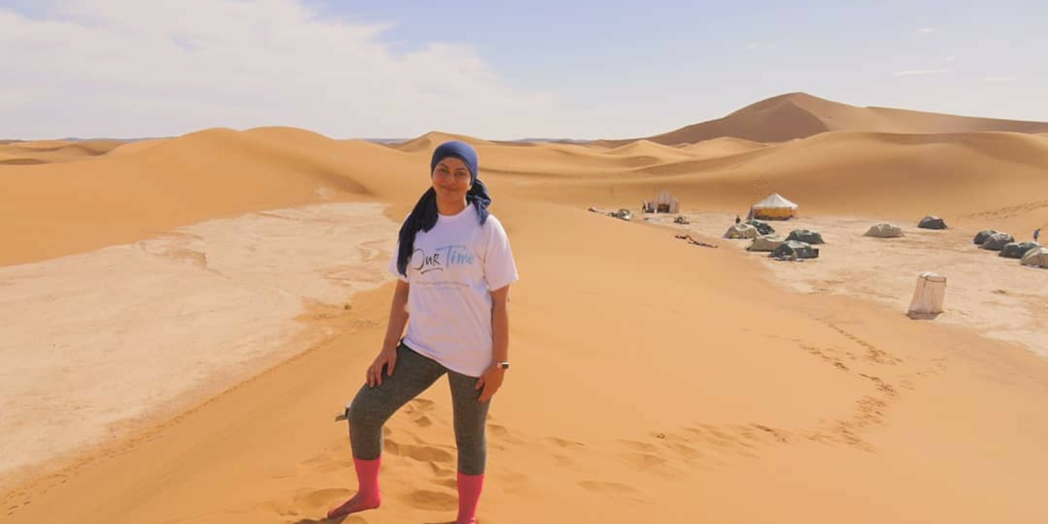 Photo of Ambeya standing in the Sahara desert wearing an Our Time T-shirt