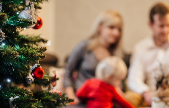 Parents and child next to a Christmas Tree