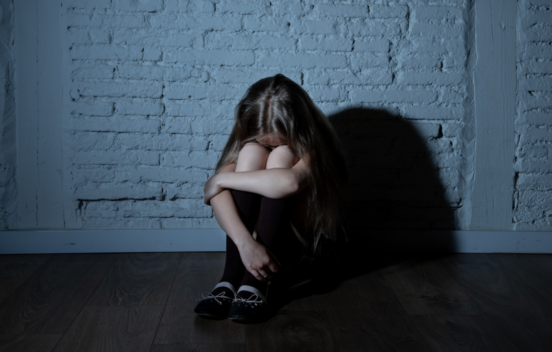 young girl in shadow hugging her knees whilst on the floor.