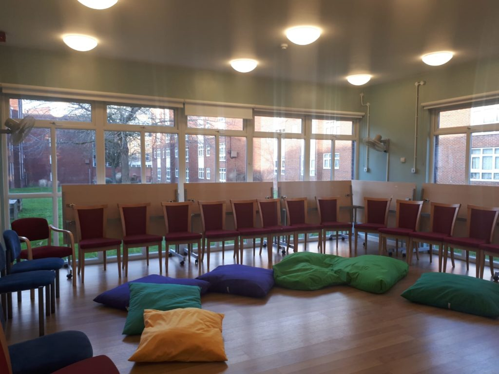 Image of a KidsTime workshop before the families arrived with chairs in a horseshoe layout and some beanbags on the floor.