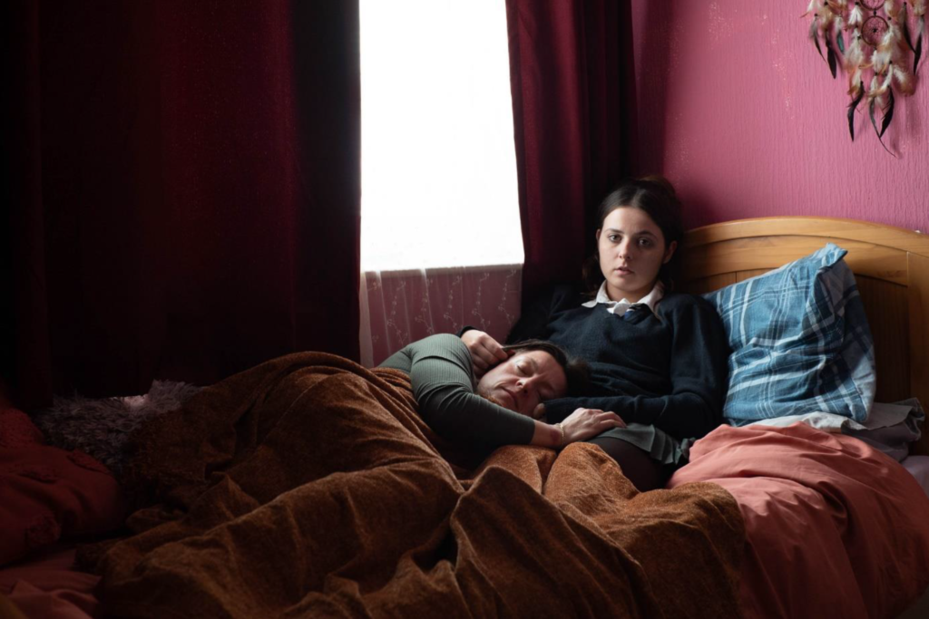 A girl an her Mum lying in bed with pink walls and a window behind