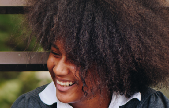 Photo of a girl laughing, head turned to her right