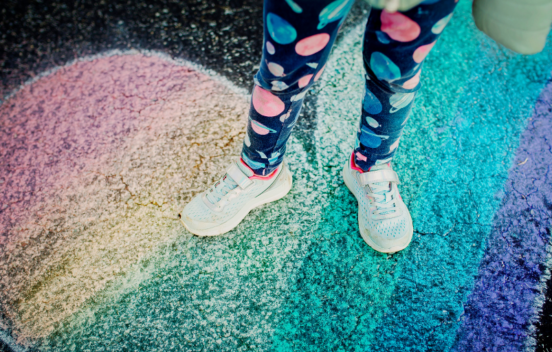 Child standing on a chalk-drawn rainbow heart