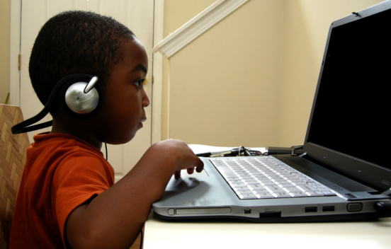 Child with headphones on looking at a laptop screen