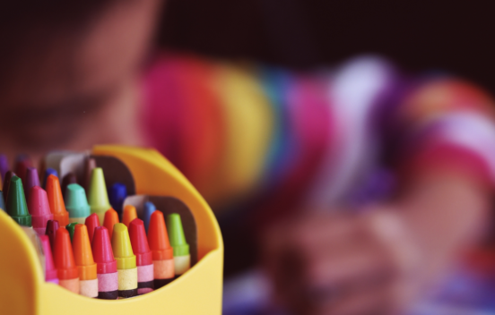Child in rainbow jumper in background, coloured crayons in foreground