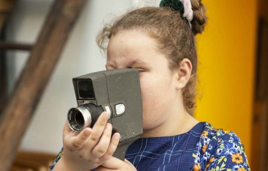 Teenage girl holding up old fashioned camera