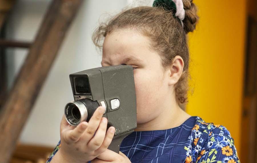 Teenage girl holding up old fashioned camera