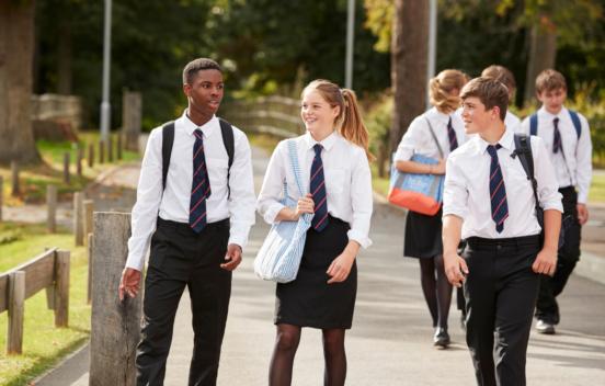 Three UK school children walking and laughing