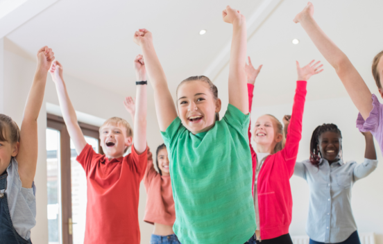 Group of children in coloured t shirts with their hands in the air and smiling