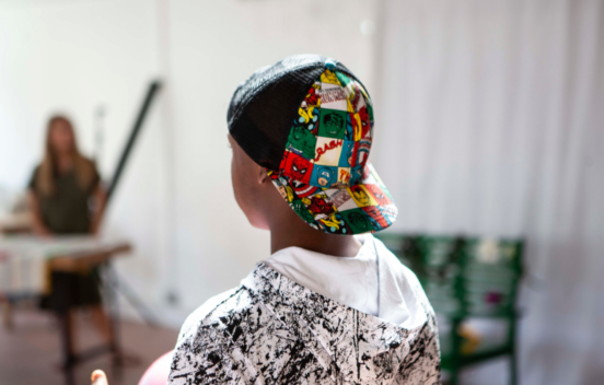 Back of a boy's head who is wearing a colourful baseball cap back to front and graphic hoodie