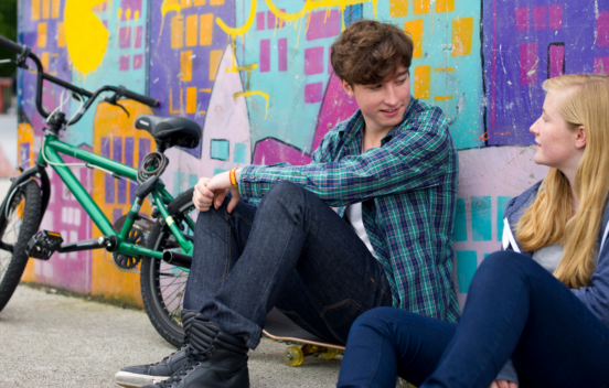 A teen boy and girls sitting down, leaning against a brightly coloured wall, chatting to each other