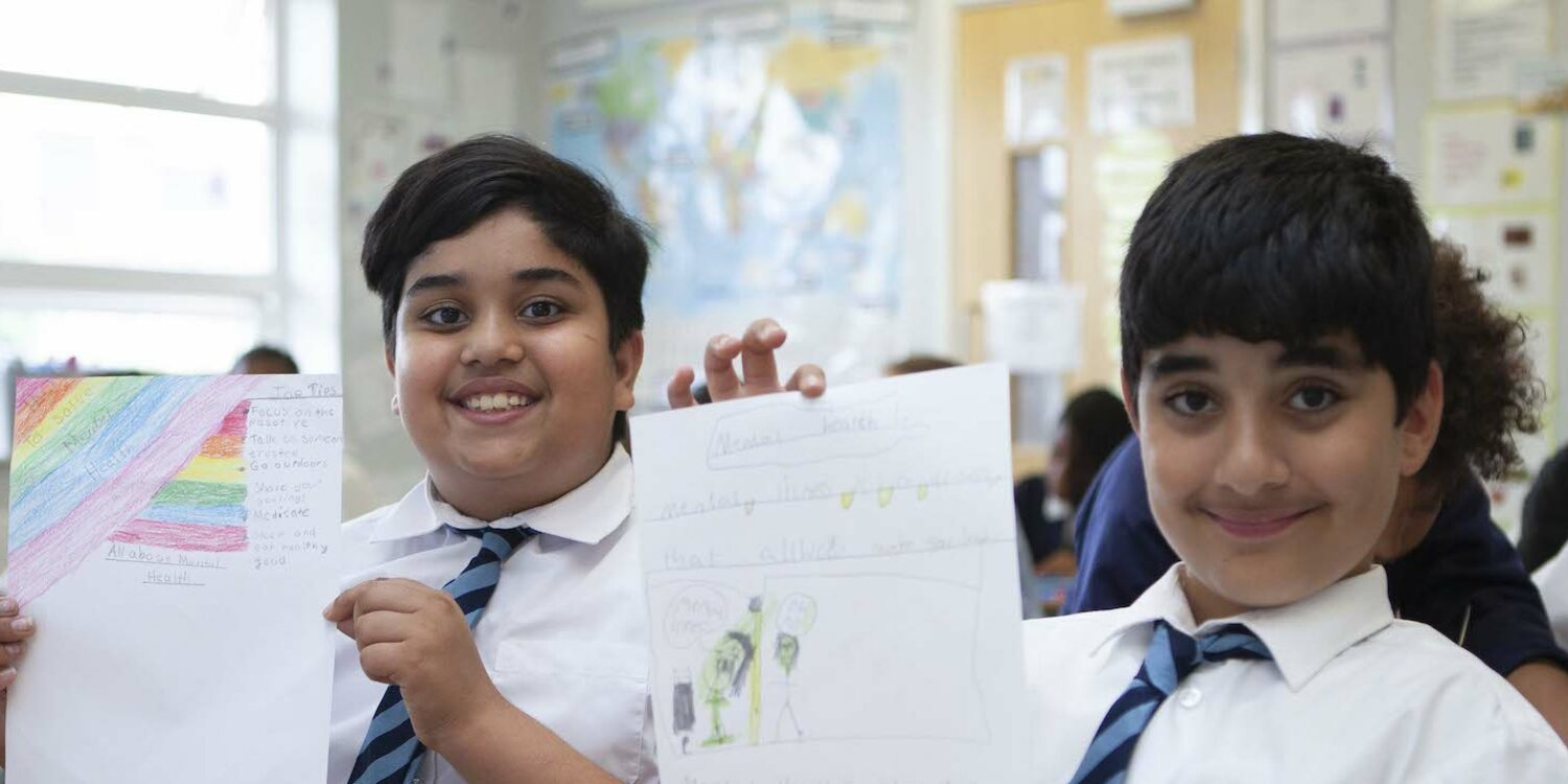 Two pupils holding up their work