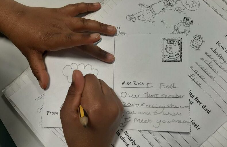Student completing postcard activity